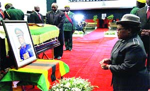 FARE THEE WELL . . . Vice-President Joice Mujuru kneels before a portrait of her late husband Retired General Solomon Mujuru and the casket containing his body at Stodart Hall in Mbare on August 21, 2011. by Pan-African News Wire File Photos