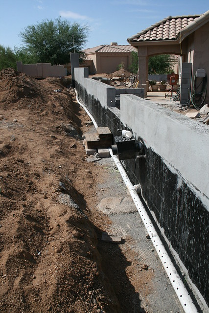 Stucco above grade waterproof tar below grade french for French drain collection box