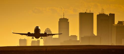 sunset boston skyline plane airport takeoff