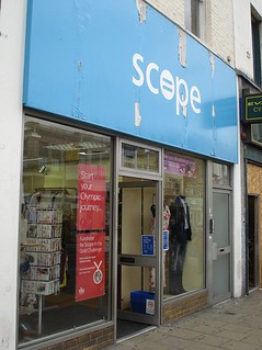 "An oblique view onto a shop frontage with full-length glass windows and a sign above reading ""Scope"" in white letters on a light blue background.  The sign is peeling away in several places."
