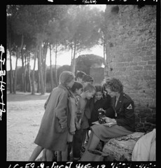 [Toni Frissell, sitting, holding camera on her lap, with several children standing around her, somewhere in Europe] (LOC)