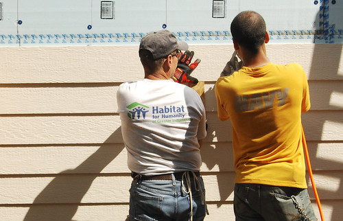 USS Shoup Sailor works with a volunteer on a Habitat for Humanity home building project