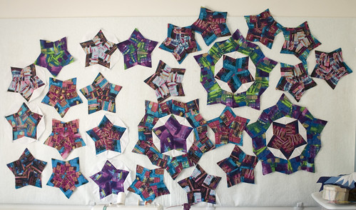 25 stars done. My pile of cut-but-unassembled pieces for this quilt is starting to get a bit more manageable.  I am thinking very very hard about disassembling the green-ringed star to get some green stars. It was a neat idea, but I think the pattern would be better served by having cohesively-patterned stars from all sections of the fabric, and leaving the borders between them to be variegated and random.  I think.  Check back again tomorrow to see if I've changed my mind.