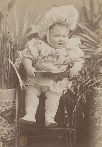 Champion prize baby in a wooden high chair
