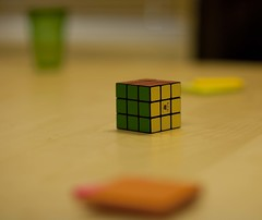 hand(0.0), number(0.0), rubik's cube(1.0), yellow(1.0), green(1.0), close-up(1.0), toy(1.0),