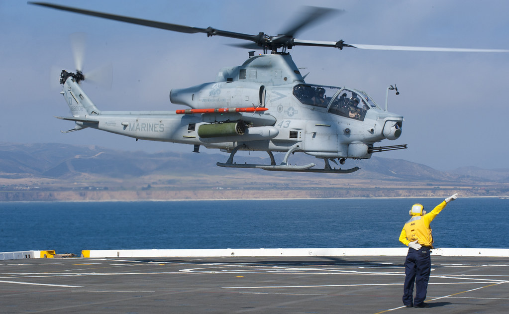 Sailor guides a Marine Corps AH-1Z Viper attack helicopter off the flight deck of USS New Orleans