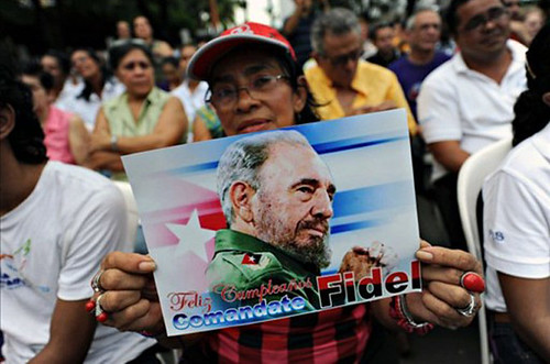 Cuban woman holds post of Comrade Fidel Castro during a 85th birthday celebration for the revolutionary leader. Fidel was president and head of the Communist Party of Cuba for decades. by Pan-African News Wire File Photos