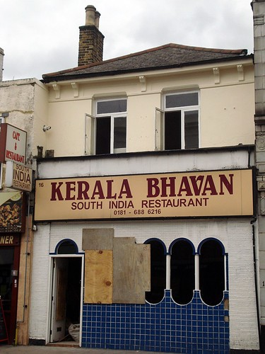 "The same building as above, still a restaurant, still with the same five-oval window, but now painted in pale cream and white with blue tiles beneath the window.  Part of the window is boarded up, and building materials are just visible inside the open door. The sign above now reads ""Kerala Bhavan / South India Restaurant / 0181 - 688 6216""."