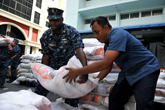 BANGKOK (Oct. 26, 2011) Chief Cryptologic Technician (Collection) Daniel Leonard, assigned to USS Mustin (DDG 89), helps a Thai Red Cross Society volunteer move bags of rice to prepare packaged goods kits during a community service event. (U.S. Navy photo by Mass Communication Specialist 1st Class Jennifer A. Villalovos)