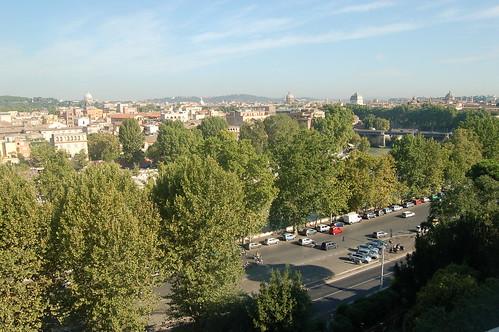 Vorne das Tiberufer mit Bäumen, im Hintergrund der Peterdom und die anderen Gebäude in Rom