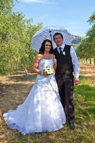 Artistique Photography by Nicolette - the bride and groom under an umbrella.