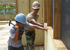 In this file photo, Sylvester Route, one of 16 local apprentices receiving basic construction skills instruction, under the guidance of Builder Constructionman Adam Kristunas of Naval Mobile Construction Battalion (NMCB) 133, installs T1-11 siding on a new classroom at the Palikir Public School in Pohnpei, Federated States of Micronesia, Sept. 29. (U.S. Navy photo by Lt. Wesley Howard)