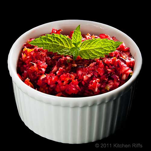 Cranberry Jalapeno Relish in white ramekin on black background with mint garnish