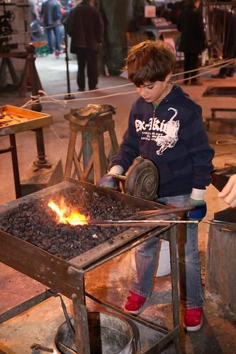 Apprenti forgeron à la forge