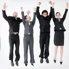 Four business people jumping mid air with raised arms, portrait