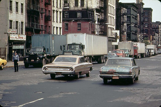 More New York fun from 1973!  A 1960s Ford Galaxie and a battered early 1960s Plymouth Valiant (fixed with bondo) cruise along Canal Street with peeling pavement. The Galaxie has a rope to lock the trunk. New York.