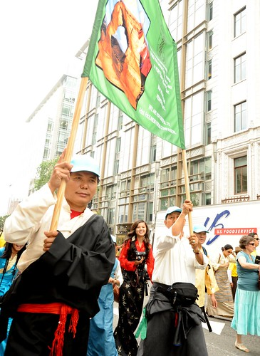 Tibetan men from the Kham region of Tibet hold a sign, female Tibetan photographer wearing a black chuba, Happy Birthday to His Holiness the Dalai Lama Parade, Tibetans at Kalachakra, Washington D.C., USA by Wonderlane