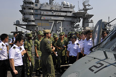 """SINGAPORE (Oct. 14, 2011) Lt. Aaron Castro, attached to the """"Chargers"""" of Helicopter Anti-Submarine Squadron (HS) 14, gives sailors from the Republic of Singapore Navy a tour of the USS George Washington (CVN 73) flight deck. (U.S. Navy photo by Mass Communication Specialist Third Class Marcus D. Mince)"""