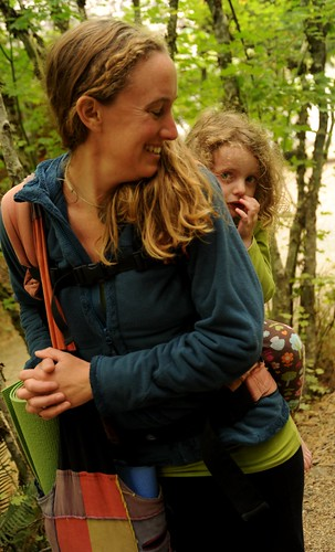 Riding piggyback, a shy young girl and her mom, yoga mats, colorful patchwork bag, forest, Breitenbush Hot Springs, Breitenbush, Marion County, Oregon, USA by Wonderlane