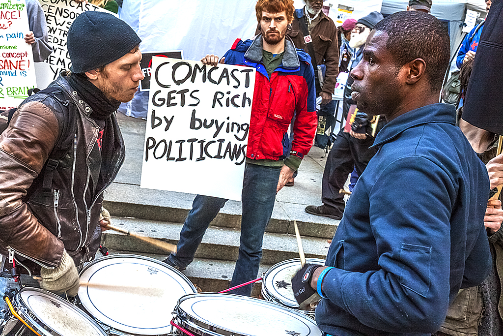 Drummers-and-man-with-sign-against-Comcast--Center-City