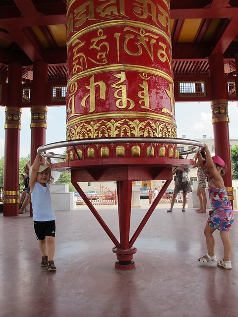 Kids spinning a prayer wheel at a pagoda in Elista, Republic of Kalmykia, Russia - the only Buddhist region of the European continent