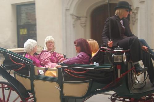 Im Fiaker sitzt eine Gruppe fröhlicher junger Männer in historischen Kostümen