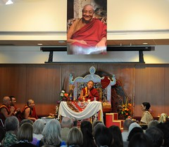 Dilgo Khyentse Yangsi Rinpoche saying prayers, throne, a photograph of his prior incarnation above, Dagmo Kushog Sakya (on the right), (monks on left) Rabjam Rinpoche, Changling Rinpoche, Mathieu Ricard, Vancouver BC, on stage, Lotus Speech Canada