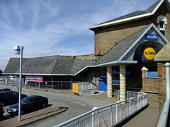 "A closer view of the peaked-roof building shown earlier, with ""Fitness First"" branding in place of ""easyGym"", and significant damage to the roof tiles."