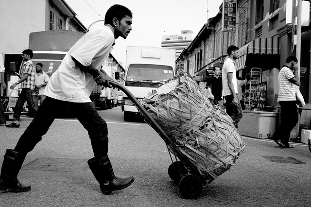 Working on a Sunday - a migrant worker pushes a cartload of goods at Little India.