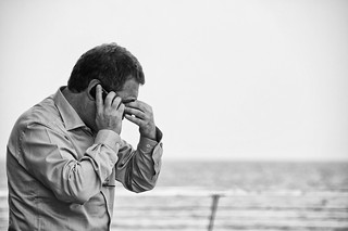 Worried man talking on cellular phone