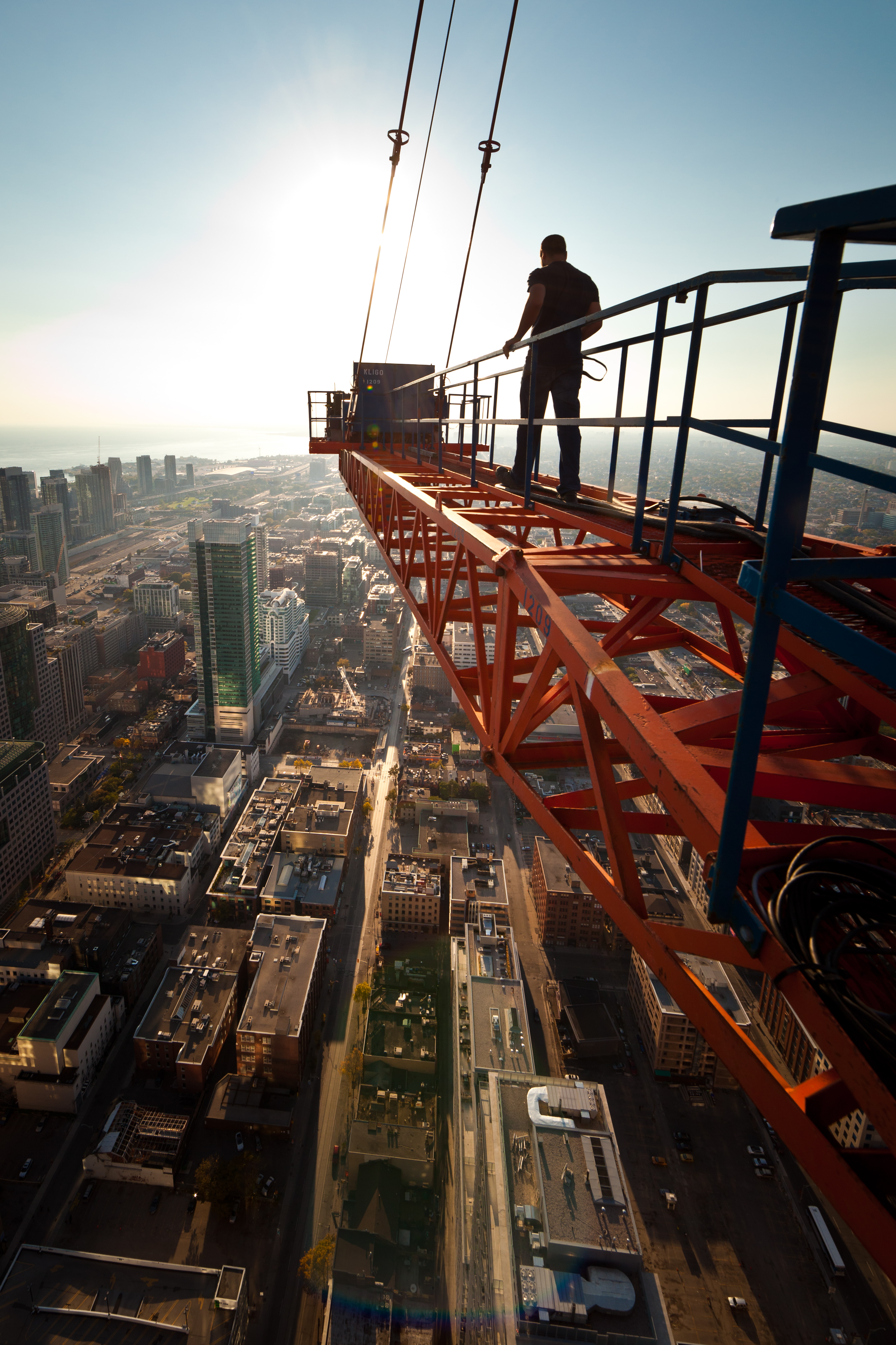 man walking on a crane into the sun