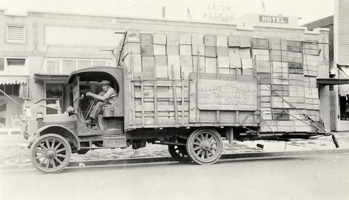 People driving trucks, loaded with produce! 1925