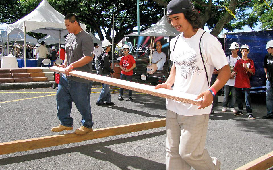 <p>Students practiced the fine art of balancing while carrying a wood beam in the carpentry area.</p>