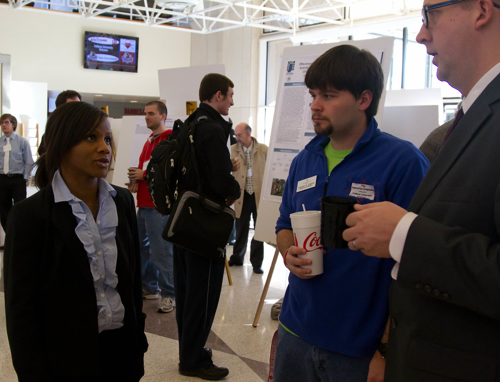 Psychology majors Jeremy Gibson and Brian Arwood (center and right) discuss undergraduate research with a fellow attendee