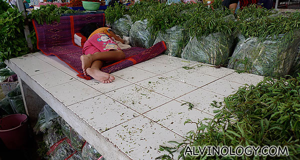 A child resting at a vegetable stall