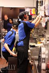 Deux jeunes hommes cuisinant des hamburgers