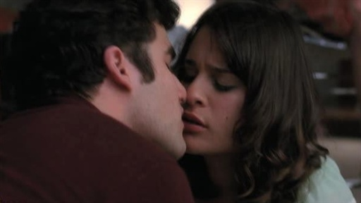 A man with dark curly hair and a dark red shirt leans in to kiss a woman with wavy brown hair. Their noses are touching and their eyes are closed.