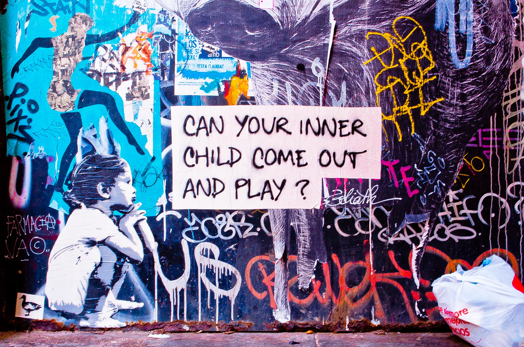 graffiti, a child sitting with her knees pulled up to her chest, hands on knees, chin on hands, next to the words