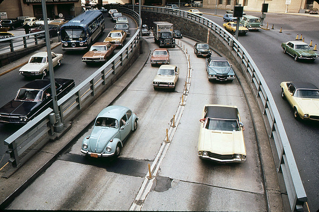 1960s and 1970s car heaven. I spy a 1960s Chevy Impala, a 1971 Camaro, a Chevy Nova, a Datsun (?), Cadillac, a GMC Flxible bus, a 1960s Dodge Van and lots of VW Beetles.  What do U see? Brooklyn Battery Tunnel traffic. New York. May 1973