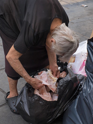 Greek pensioner looking through rubbish for leftover food