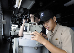 SOUTH CHINA SEA (Oct. 7, 2011) Republic of Korea (ROK) navy Lt. Wook Hyun Min uses an alidade aboard USS Cowpens (CG 63). (U.S. Navy photo by Mass Communication Specialist 1st Class N. Ross Taylor)