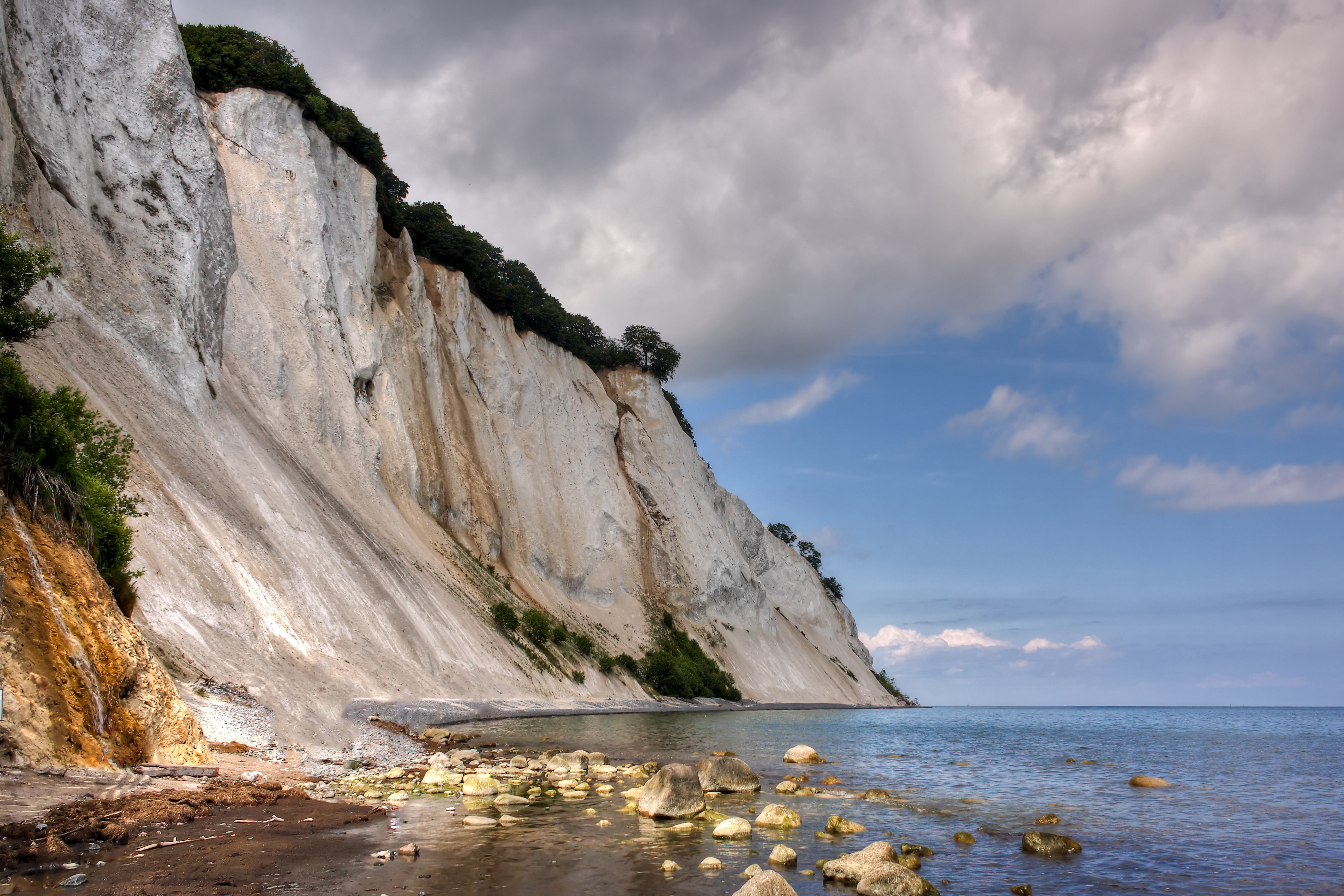 Møns Klint, English: the Cliffs of Møn. The chalk forming the cliffs consists of the remains of shells from millions of microscopic creatures (coccolithophores) which lived on the seabed over 70 million years ago. As a result of huge pressure from glaciers moving west, the terrain was compacted and pushed upwards, forming a number of hills and folds. When the ice melted at the end of the last ice age about 11,000 years ago, the cliffs emerged. They form part of the same deposits as the cliffs of Rügen, Germany, on the other side of the Baltic. Today, it is possible to find fossils of various types of shellfish as the sea continues to erode the chalk. Erosion also caused one of the highest points on the cliffs, the Sommerspir, to fall into the sea in 1998, and in January 2007, there was an even larger landslide around the Store Taler, in the northern part of the cliffs, creating a 300-m long peninsula of chalk and fallen trees stretching out into the sea below. source: en.wikipedia.org/wiki/M%C3%B8ns_Klint  All Rights Reserved © René Eriksen. Please do not use my pictures outside the Flickr, without my permission.