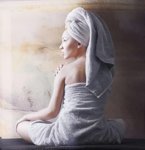 ragazza seduta di spalle con asciugamano intorno al corpo e ai capelli