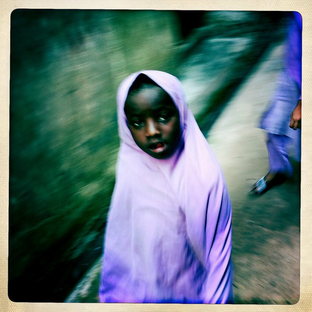 Young Veiled Girl Passing By A Street Of Lamu, Kenya
