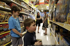 boys shop for toys while mom & grandma look on