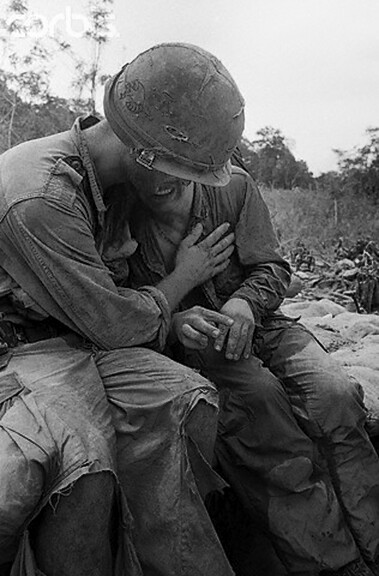 An unidentified soldier breaks down under the stress of combat and is comforted by a comrade following recent battle 55 miles west of Pleiku, South Vietnam, 1967, unattributed