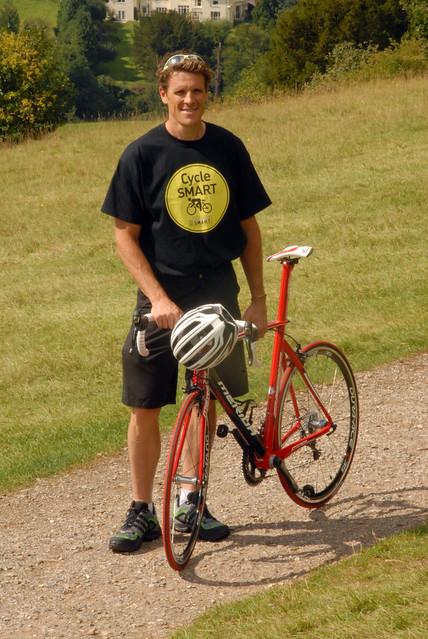 James Cracknell stood next to a bike