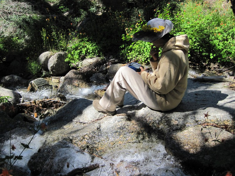 Vicki relaxing next to the stream at Columbine Camp