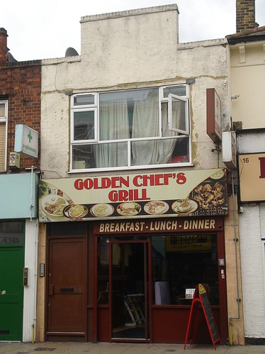 "A small two-storey building with a cafe on the ground floor and a large net-curtained window on the first floor. The roof profile features a large sticking-up rectangular detail. The cafe frontage is timber-framed and painted a dark brown. A sign above reads ""Golden Chef's Grill"" in red letters on a light brown/yellow background."