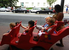 Privileged childhood, kids in a red 6 seater stoller with nanny, bye bye buggy, near Verizon Center, Kalachakra for World Peace, Washington D.C., USA